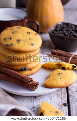 Homemade Pumpkin Spice Cookies with chocolate chips or drops with brown cup of milk on Halloween,cinnamon sticks. Wooden background