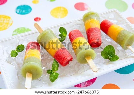 Homemade pureed fresh fruit popsicles with strawberry, mango, peach and kiwi - stock photo
