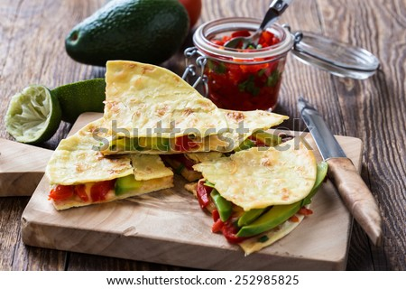 Homemade quesadilla,  corn tortilla filled with cheese,  avocado, chopped onion,  chiles, and served with red salsa - stock photo