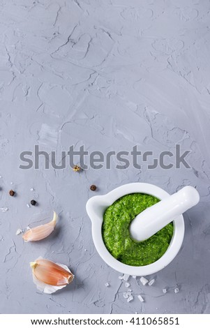 Homemade ramson green pesto sauce in white ceramic mortar with pestle over gray textured background with sea salt, pepper ang garlic. Top view with copy space - stock photo