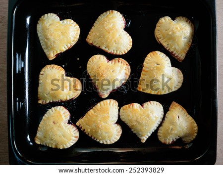 Homemade Raspberries, lemon Pies crust hearts on a tray - stock photo