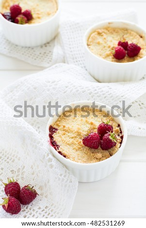 Homemade raspberry crumble on white wooden background