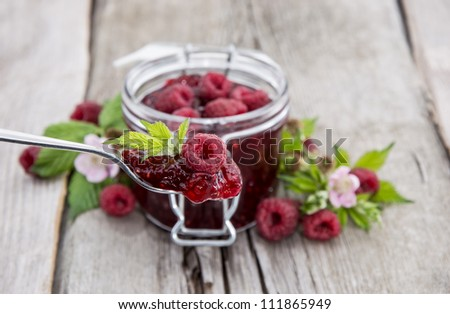 Homemade Raspberry Jam against a wooden background - stock photo