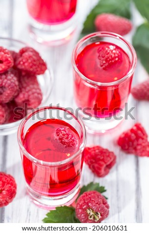 Homemade Raspberry Liqueur in a glass with some fresh fruits