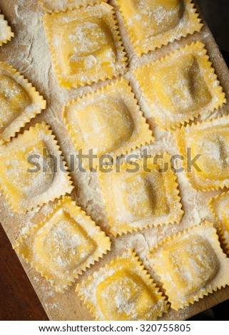 Homemade ravioli on a wooden board - stock photo