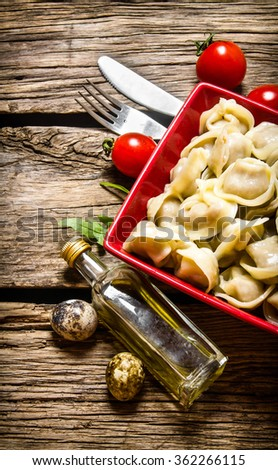 Homemade ravioli prepared with tomatoes and olive oil.  On the wooden background. Top view - stock photo