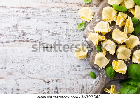 Homemade raw Italian saccottini filled with green pesto on wooden vintage cutting board with basil leaves. Selective focus. Top view. With copy space for text. - stock photo