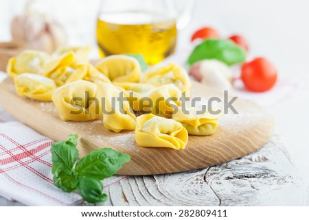 Homemade raw Italian tortellini and basil leaves on a white wooden background, selective focus - stock photo