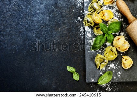 Homemade raw Italian tortellini and basil leaves on dark vintage background - stock photo