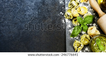 Homemade raw Italian tortellini, basil leaves and pesto on dark vintage background - stock photo
