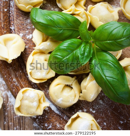 Homemade raw Italian tortellini on wooden vintage cutting board with a rolling pin. Selective focus. Top view. - stock photo