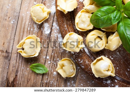Homemade raw Italian tortellini on wooden vintage cutting board with a rolling pin. Selective focus. - stock photo
