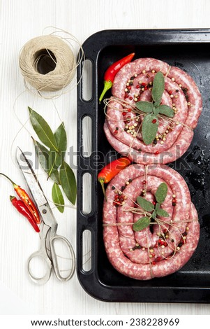 homemade raw sausage with herbs aromatic & fresh red pepper. ready for cooking. on baking tray - stock photo