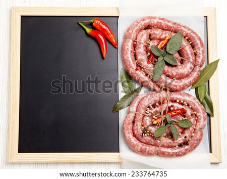 homemade raw sausage with herbs aromatic & fresh red pepper. ready for cooking. on chalkboard - stock photo