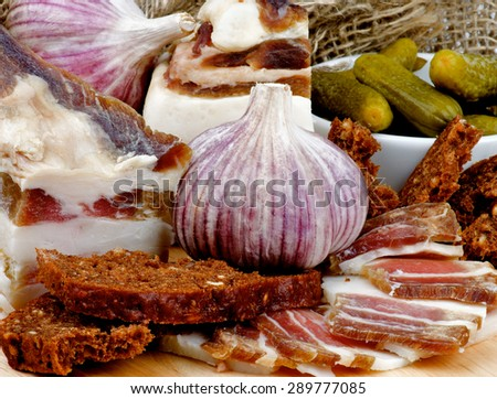 Homemade Raw Smoked Bacon with Brown Bread, Garlic and Gherkins closeup on Cutting Board - stock photo