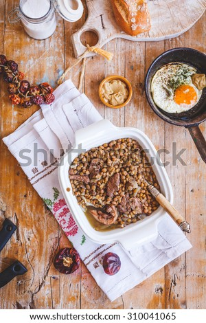 Homemade real meat from lentils with  beef meat served on ceramic bowl from above on a rustic kitchen table with chapatti sliced and fried egg in pan. Rustic style. Mediterranean diet. - stock photo