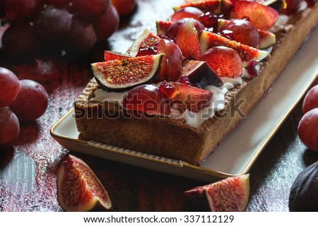 Homemade rectangular Tart with red Grapes, Figs and Whipped cream in white ceramic plate over red wooden table. Dark rustic style, natural day light. - stock photo