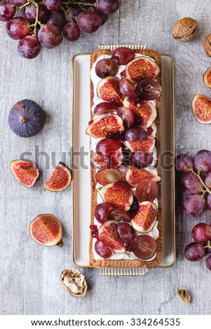Homemade rectangular Tart with red Grapes, Figs, walnuts and Whipped cream in white ceramic plate over white wooden table. Rustic style. - stock photo