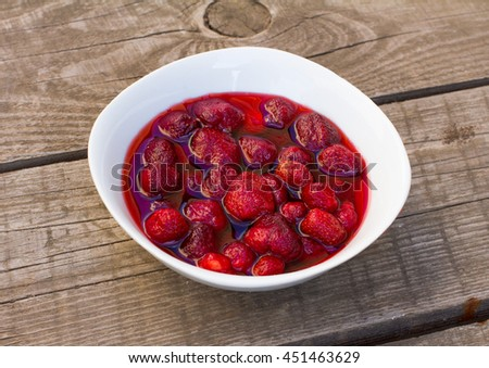 Homemade red strawberry jam on white plate on a wooden background - stock photo