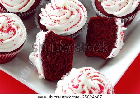 Homemade Red Velvet Cupcakes with white frosting and red sprinkles on a red background
