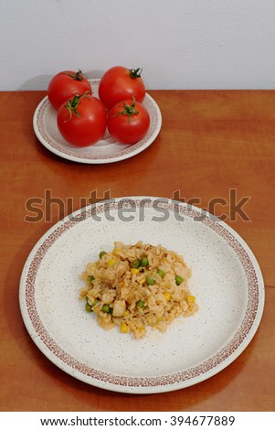 Homemade risotto with corn, peas and chicken on a plate on the wooden table - stock photo