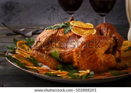 Homemade roasted whole chicken with parsley and oranges, selective focus.