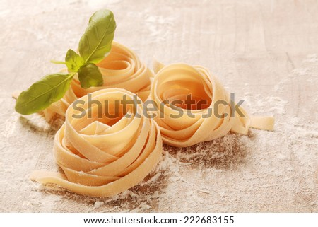 Homemade Rolled Flat Fresh Fettuccine Pasta on Wooden Table with Flour. - stock photo