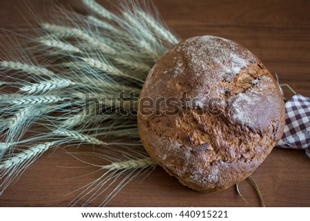 Homemade round bread on barley ears closeup - stock photo