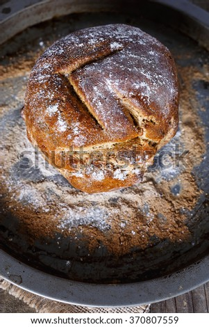 Homemade rustic bread on a baking tray over wooden background