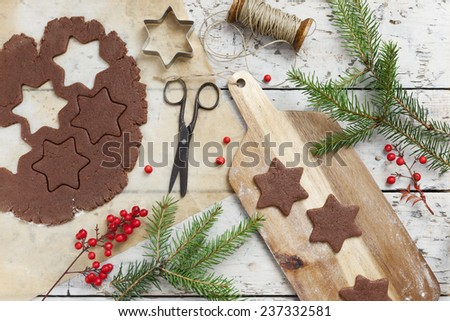 homemade rustic gingerbread star shaped cookies for Christmas on table with pine twigs and red berries - stock photo