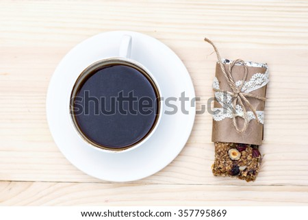 Homemade rustic granola bars with dried fruits and handmade packaged and cup of coffee on wooden background - stock photo