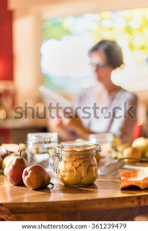 Homemade rustic jar of fruits with pears around on wooden table. The pears are canned to preserve their freshness. Shot with flare. A woman with tablet is sitting in the kitchen in the blur background - stock photo