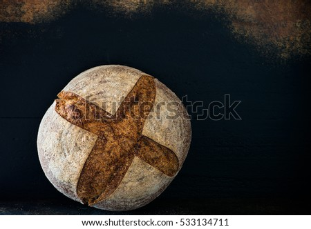 Homemade rye artisan sourdough bread over dark background, copy space
