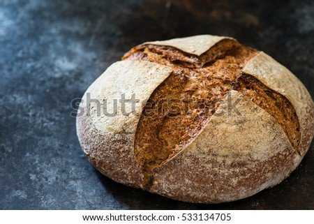 Homemade rye artisan sourdough bread over dark background, selective focus, closeup