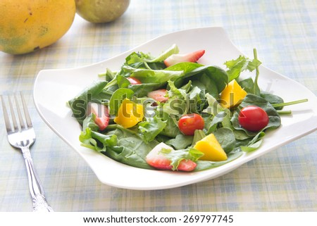 Homemade salad with spring greens spinach, fruits and vegetables. Arranged in a white bowl on a table covered with picnic table cloth with fork - stock photo