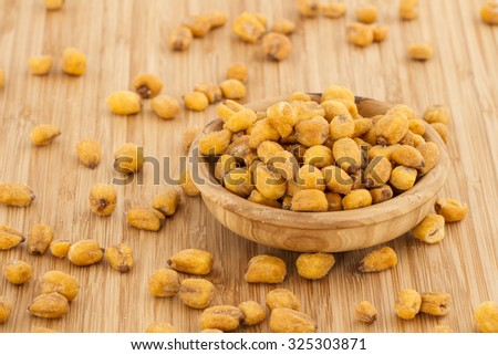 Homemade Salty Corn Nuts in a Bowl on Bamboo background - stock photo