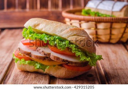 Homemade sandwich with fresh tomatoes and chicken breast in basket on wooden background. Selective focus. Picnic concept - stock photo