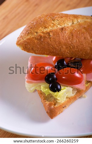 Homemade sandwich with ham, salad and tomatoes in white bread baguette - stock photo