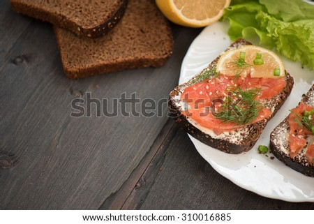 Homemade sandwich with salmon and rye bread , butter lemon, and lettuce for breakfast - stock photo