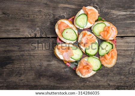 Homemade sandwiches with pink salmon and cucumber. Plate of snack on wooden background with copy space. Top view image menu background - stock photo