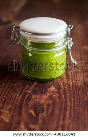 Homemade sauce or jam with kiwi fruit, gooseberry, spinach in a jar on a wooden table, selective focus - stock photo