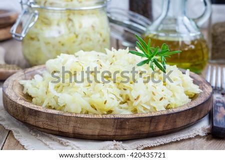 Homemade sauerkraut on a wooden plate - stock photo