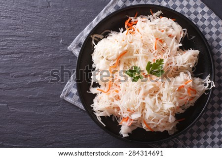 homemade sauerkraut with carrot in a black plate horizontal view from above