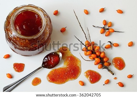 Homemade sea-buckthorn jam in a jar with fresh berries and spoon on a white table. Photo above. - stock photo