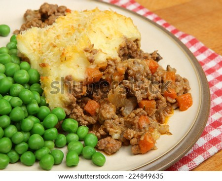 Homemade shepherds pie served with peas. - stock photo