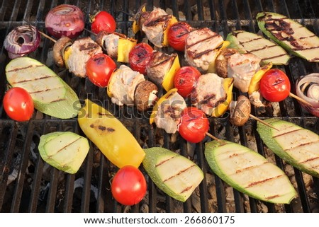 Homemade Shish Kabobs BBQ with Meat, Peppers, Tomatoes and Mushroms With Grilled Vegetables   Zucchine, Eggplant and Onions on Hot Grill. Snack For Summer Barbecue Outdoor Party. - stock photo