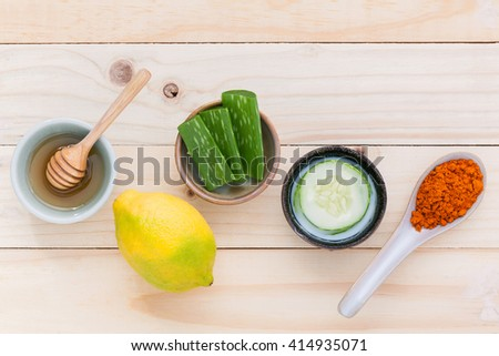 Homemade skin care and body scrub with natural ingredients  aloe vera ,lemon,cucumber ,turmeric powder and honey set up on on wooden background.