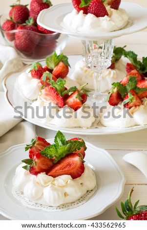Homemade small strawberry pavlova meringue cakes with mascarpone cream and fresh mint leaves on white plate - stock photo