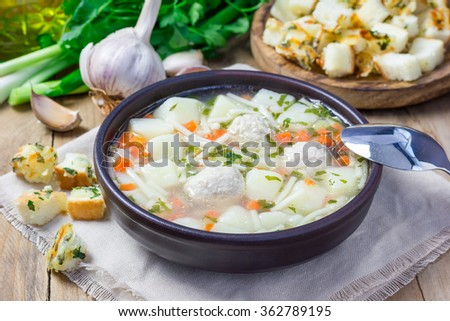 Homemade soup with meatballs and vegetables, served with cheese-garlic-parsley croutons