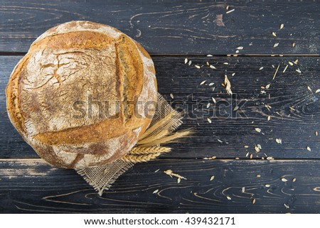 Homemade sourdough bread loaf decorated with burlap and cereal grains and ears - stock photo